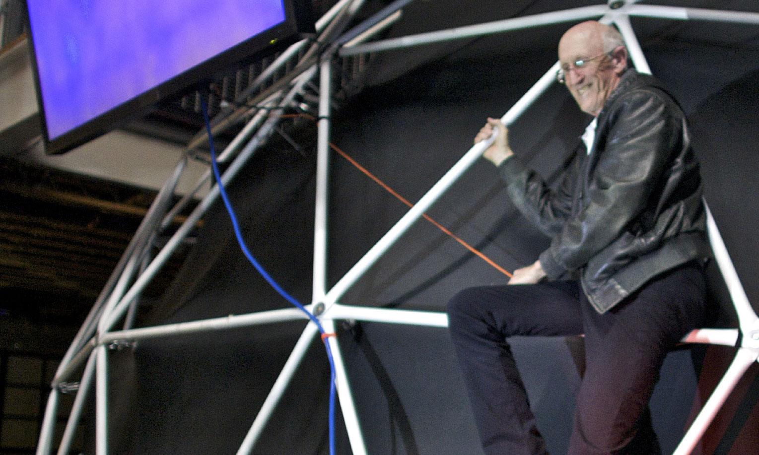 Stewart Brand climbs the geodesic dome